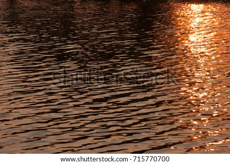 Ripples on the surface of sunset in water.