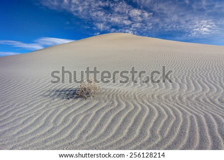 Ripples sand dune lead to clouds in the sky - stock photo