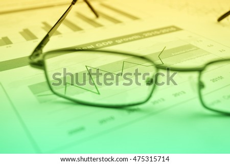 Rise up graph with glasses on financial chart and graph, Success business concept