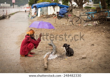 RISHIKESH, INDIA - JAN 02: An unidentified sadhu baba get warming on fire with two small dogs on January 02, 2015. Rishikesh it's a spiritual city where you can find many sadhu baba. - stock photo