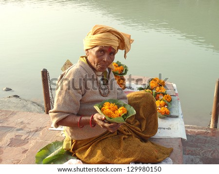 RISHIKESH, INDIA - JUNE 2012: Unidentified woman sells offerings for Ganges on June 2012 in Rishikesh on occasion of Ganga Puja celebration. - stock photo