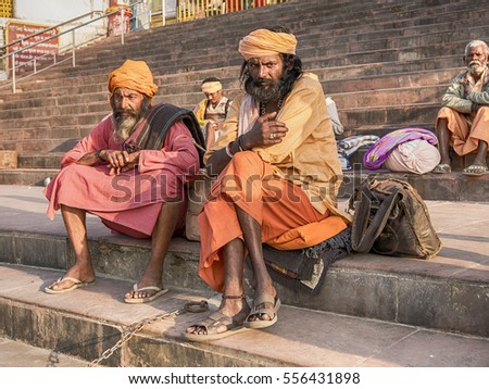 RISHIKESH, INDIA - NOVEMBER 16, 2016: Two sadhus, or religious men, sit in colorful attire the steps of a ghat near the Ganges River in the holy city of Rishikesh.