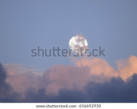 Rising full moon in sunlit clouds over east Thailand