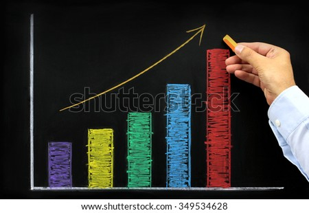 Rising graph with colorful chalk on blackboard - stock photo
