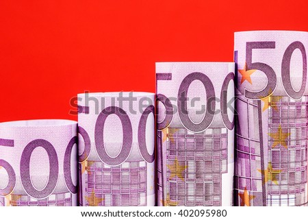 rising steps made of 500 euro banknotes on red background - stock photo