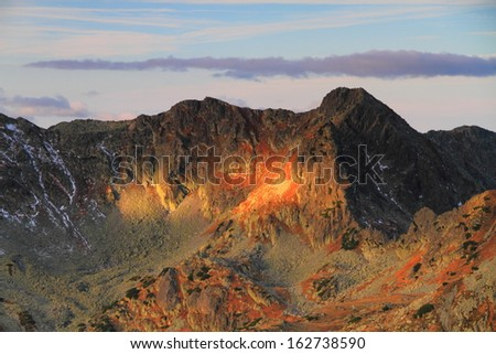 Rising sun casting red light to the mountain summits - stock photo