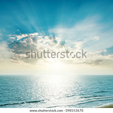 rising sun on the horizon, blue sea and clouds - stock photo