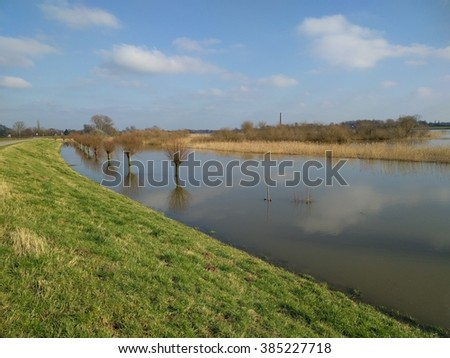 Rising water level river IJssel, dike + inundated floodplains with pollard willows and reed. Chimney brick factory at horizon. - stock photo