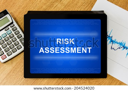 risk assessment word on digital tablet with calculator and financial graph - stock photo