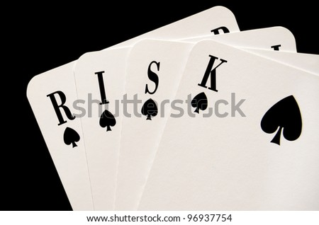 Risk concept with playing cards isolated over black - stock photo