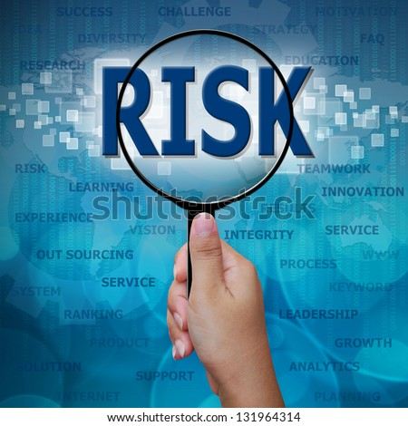 RISK in Magnifying glass on blue background