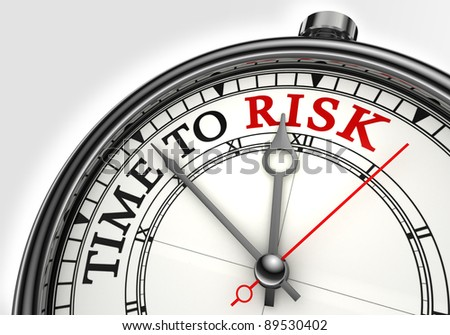 risk time concept clock closeup on white background with red and black words