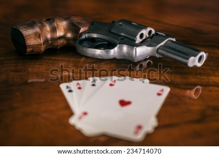 Risky gambling concept. Gun and playing cards on wooden table. - stock photo