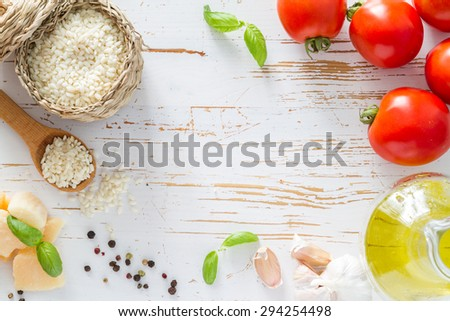 Risotto ingredients - rice, cheese, garlic, basil, oil, tomatoes, white wood background, top view