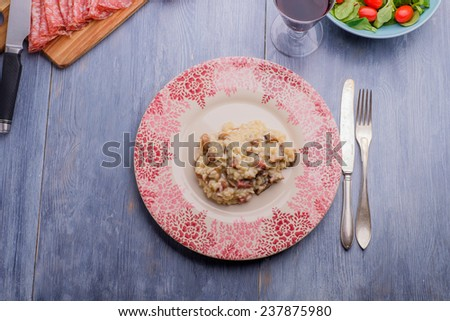 Risotto on a wood table with some antipasto in the background - stock photo