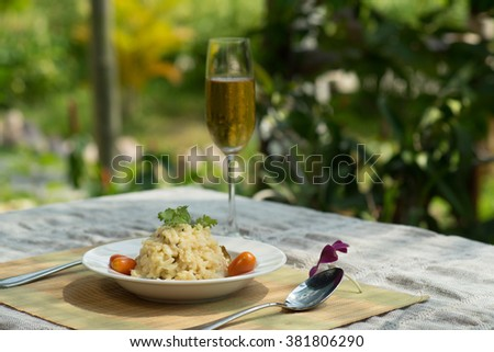 Risotto rice dish on the table with a champagne glass