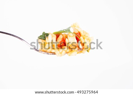 Risotto with chicken, tomatoes, bell pepper, onion, garlic and parsley on a fork on a white background