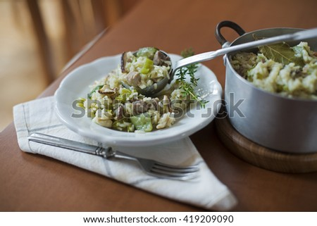 Risotto with mushrooms, meat and fresh herbs. - stock photo