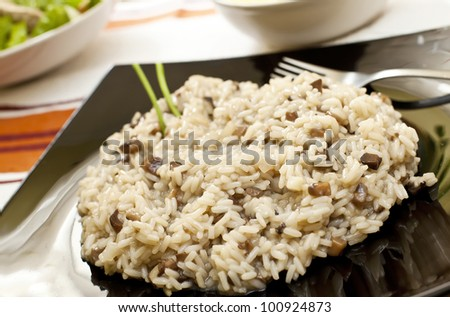 Risotto with mushrooms on black  tray and fork