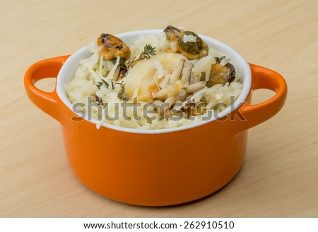 Risotto with mussels and cuttlefish served fresh thyme - stock photo