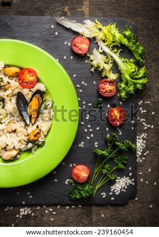 Risotto with mussels, lettuce and tomatoes on dark slate, top view - stock photo