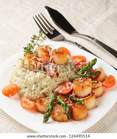 Risotto with pan seared sea scallops on served table - stock photo