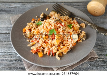 Risotto with peppers, carrots and tomatoes on a plate, tasty food - stock photo