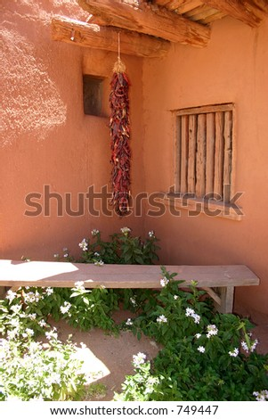 Ristra hangs in corner of centuries old adobe ranch house - stock photo