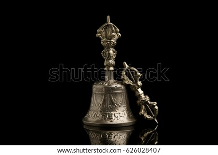 Ritual bell of well-being and happiness from metal on a black background