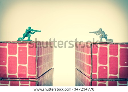 Rival toy army men aim guns at eachother atop opposing toy bricks - stock photo