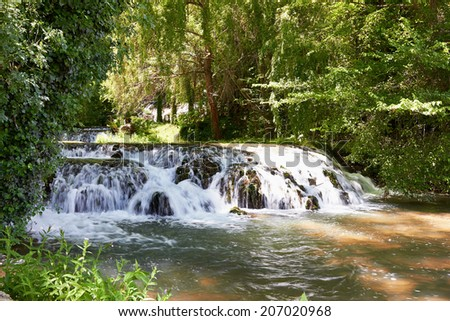 River among the rocks and green forests. Sunny summer in nature. - stock photo