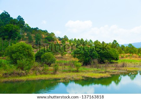River and its banks. Trees along both sides of the water. Sky is cloudy. - stock photo