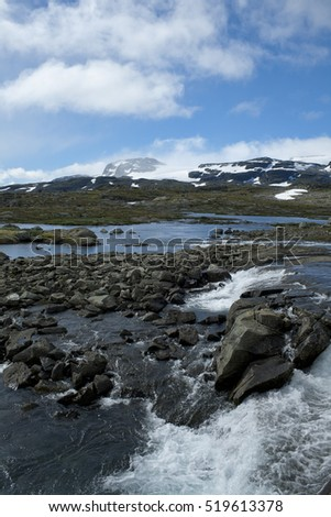 River and snowy mountain panorama. Finse, Norway.