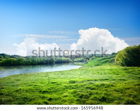 River and the field on a sunny summer day - stock photo