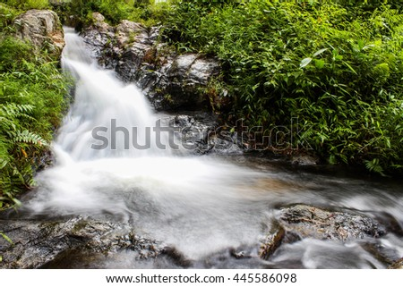 River background with small waterfalls in tropical forest - stock photo