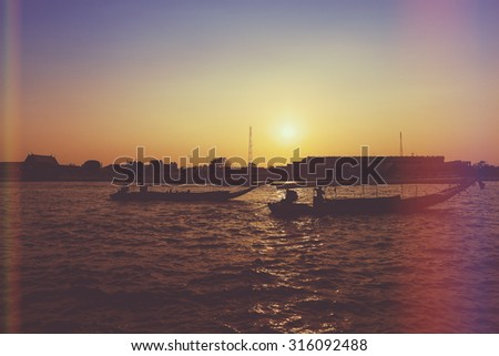 River boats crossing the Chao Phraya river in Bangkok, Thailand. with light leak filter. - stock photo