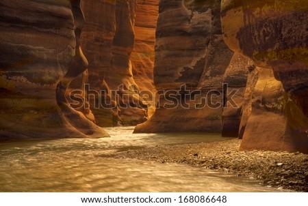 River canyon of Wadi Mujib in amazing golden light colors. Wadi Mujib is located in area of Dead Sea in Jordan - stock photo