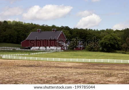 RIVER FALLS, WISCONSIN - JUNE 02, 2014: A vintage red barn and outbuildings near River Falls, Wisconsin on June 02, 2014. - stock photo