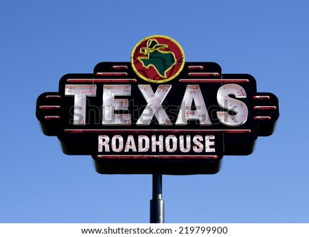 RIVER FALLS,WISCONSIN-SEPTEMBER 25,2014: Texas Roadhouse restaurant sign against a blue sky. Texas Roadhouse Corporation is headquartered in Louisville,Kentucky. - stock photo