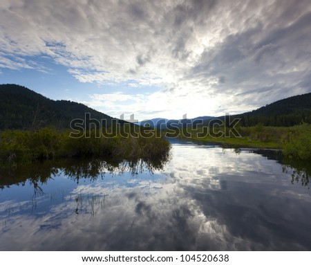 River feeding a lake at sunset - stock photo