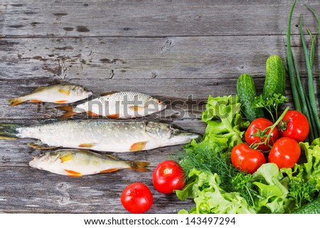 river fish with vegetables on wooden background - stock photo