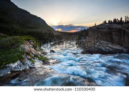 River flow at sunset near Swift Current Lake, Glacier National Park - stock photo