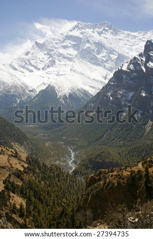 River flowing down from mountains with view over the Annapurnas - stock photo