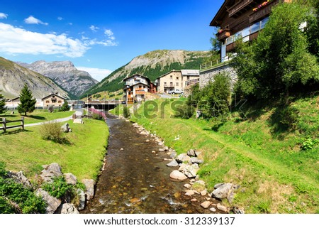 River Flowing Past Quaint Homes in Green Valley of Livigno at Foot of Italian Alps on Sunny Day with Blue Sky