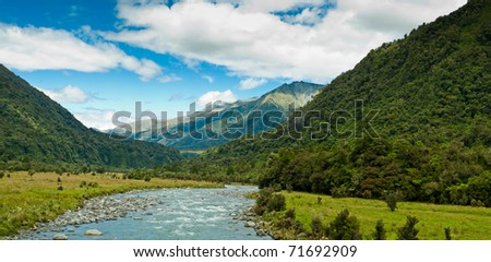 river flowing through a valley with mountain massive in the back ground - stock photo