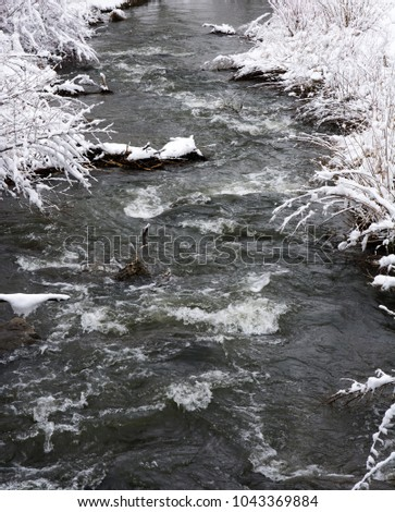 River flowing through a winter landscape with snow