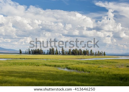 River flowing through grassy meadow in Yellowstone National Park /  Island in Yellowstone National Park /  River flowing through grassy meadow National Park - stock photo