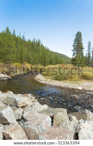 River flowing through mountain landscape in Yellowstone National Park. - stock photo