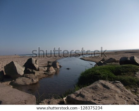river going down to beach - stock photo