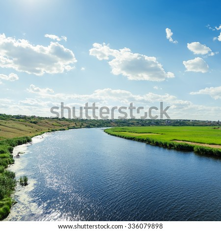 river in green landscape and cloudy sky over it - stock photo